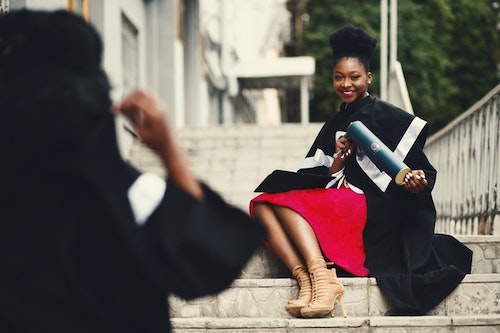 high school graduate sitting on the steps holding her diploma smiling for the camera