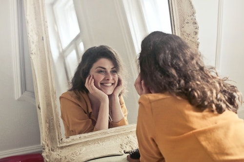 happy and smiling woman staring in the mirror at herself