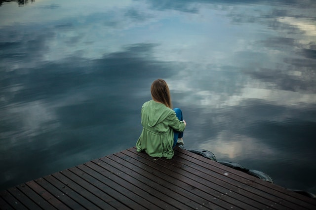 woman sitting on a dock along the water alone