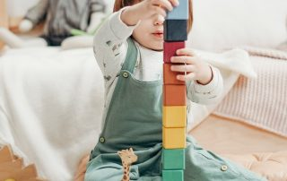 small child playing in a white room stacking blocks on top of each other
