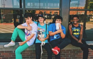 four teenagers hanging outside of a store smiling